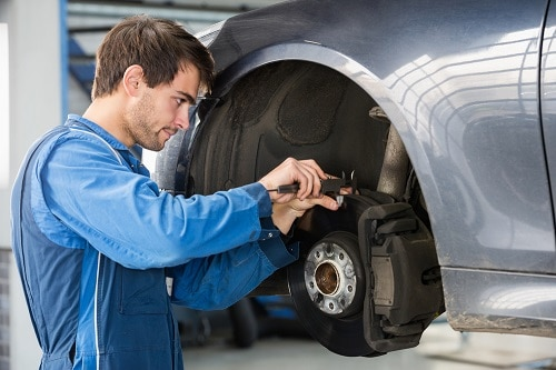 Male car mechanic examining brake disc with caliper in garage