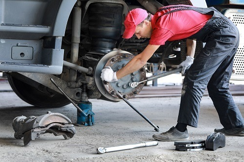 A mechanic repairs a truck- Replace brake disc and pads