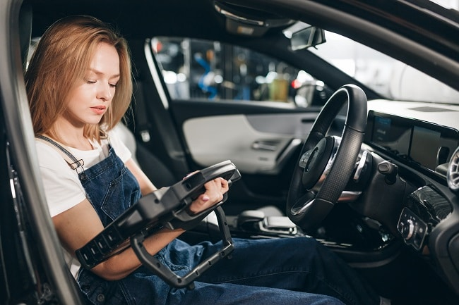 Mechanic girl use automotive diagnostic scanner when check engine flash